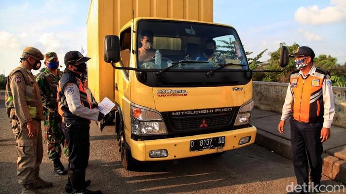 Petugas gabungan memeriksa sejumlah kendaraan yang melintas di kawasan Banjir Kanal Timur Rorotan. Kegiatan itu digelar sebagai upaya pencegahan Corona.