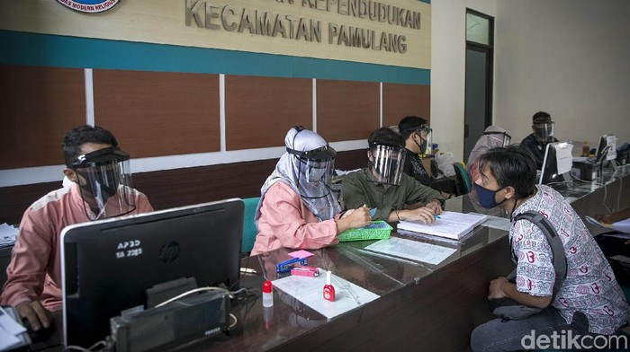 Petugas Dinas Kependudukan dan Catatan Sipil Kecamatan Pamulang, Tanggerang Selatan, tengah melayani warga dengan menggunakan Face Shield, Jumat (29/5/2020). Grandyos Zafna/detikcom
