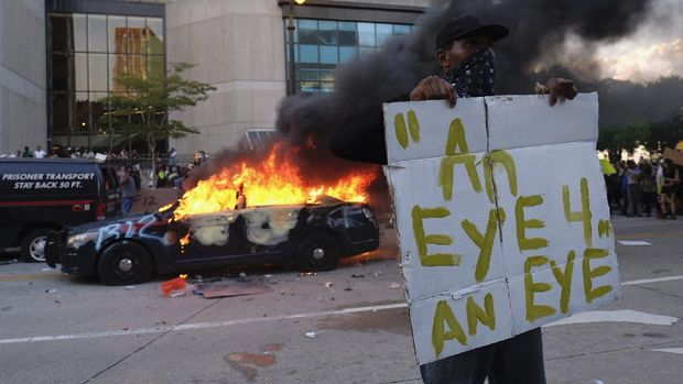 A police car burns during a protest in Atlanta, Friday, May 29, 2020. Protesters marched for George Floyd, who died after being restrained by Minneapolis police officers on Memorial Day. (Ben Gray/Atlanta Journal-Constitution via AP)
