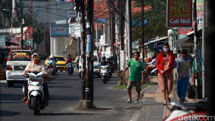 Warga menghindari tiang listrik, telepon maupun kabel serat optik yang berada di badan jalan di Jl WR Supratman, Ciputat Timur, Tangerang Selatan, Sabtu (30/5/2020). Tiang tersebut berada di badan jalan usai proyek pelebaran jalan, pertengahan 2018 lalu. Namun hingga kini belum ada proses pemindahan tiang sehingga membahayakan pengguna jalan. Selain itu, keberadaan tiang tersebut membuat pelebaran jalan belum efektif karena ada penyempitan ruang.