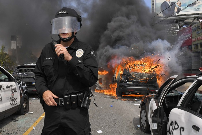 Los Angeles Police Department commander Cory Palka, right, talks to another officer as they walk by a burning police car during a protest over the death of George Floyd, Saturday, May 30, 2020, in Los Angeles. Floyd died in Minneapolis police custody on May 25.. (AP Photo/Mark J. Terrill)