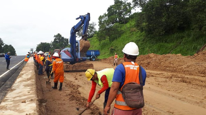 Petugas membersihkan material longsor di Tol Ungaran KM 426+600 lajur Ungaran-Semarang, Minggu (31/5/2020).