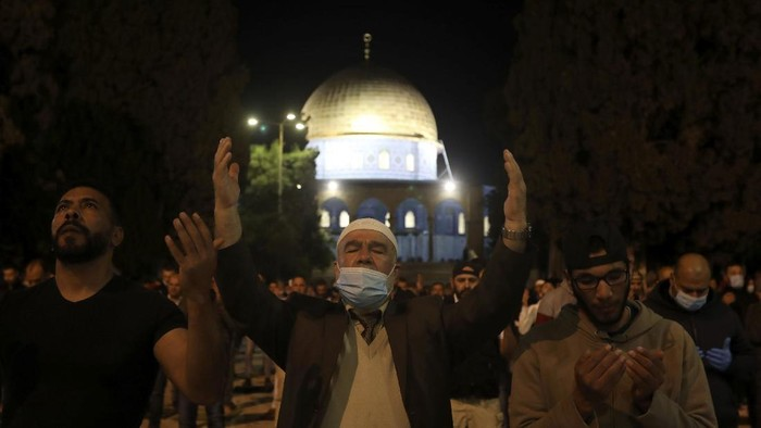 Muslim men pray next to the Dome of the Rock Mosque in the Al Aqsa Mosque compound in Jerusalems old city, Sunday, May 31, 2020.The Al-Aqsa mosque in Jerusalem, the third holiest site in Islam, reopened early Sunday, following weeks of closure aimed at preventing the spread of the coronavirus. (AP Photo/Mahmoud Illean)