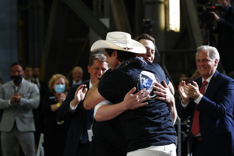 Tesla and SpaceX Chief Executive Officer Elon Musk hugs his brother Kimbal Musk during an event at the Vehicle Assembly Building on Saturday, May 23, 2020, at NASAs Kennedy Space Center in Cape Canaveral, Fla. The event occurred after a rocket ship designed and built by SpaceX lifted off on Saturday with two Americans on a history-making flight to the International Space Station. House Minority Leader Kevin McCarthy of Calif., applauds at right. (AP Photo/Alex Brandon)
