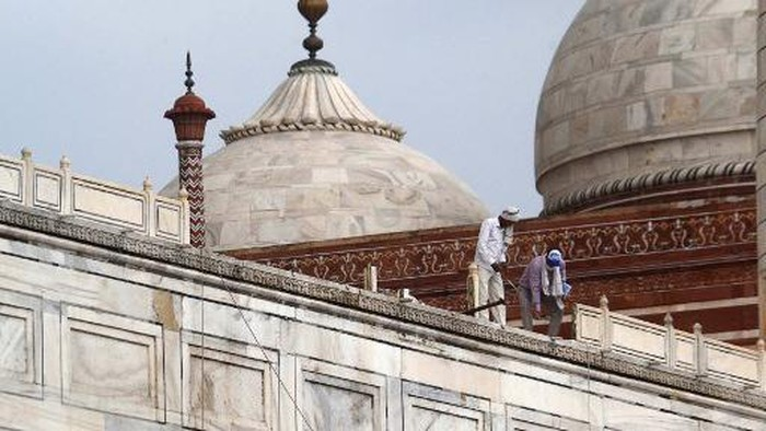 In this picture taken on May 30, 2020, workers stand on the railing of the Taj Mahal after it was damaged due to heavy rainstorm in Agra. (Photo by Pawan Sharma / AFP)