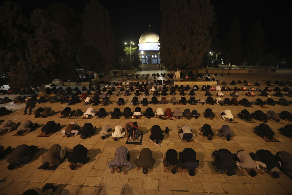 Muslim men pray next to the Dome of the Rock Mosque in the Al Aqsa Mosque compound in Jerusalem's old city, Sunday, May 31, 2020.The Al-Aqsa mosque in Jerusalem, the third holiest site in Islam, reopened early Sunday, following weeks of closure aimed at preventing the spread of the coronavirus. (AP Photo/Mahmoud Illean)