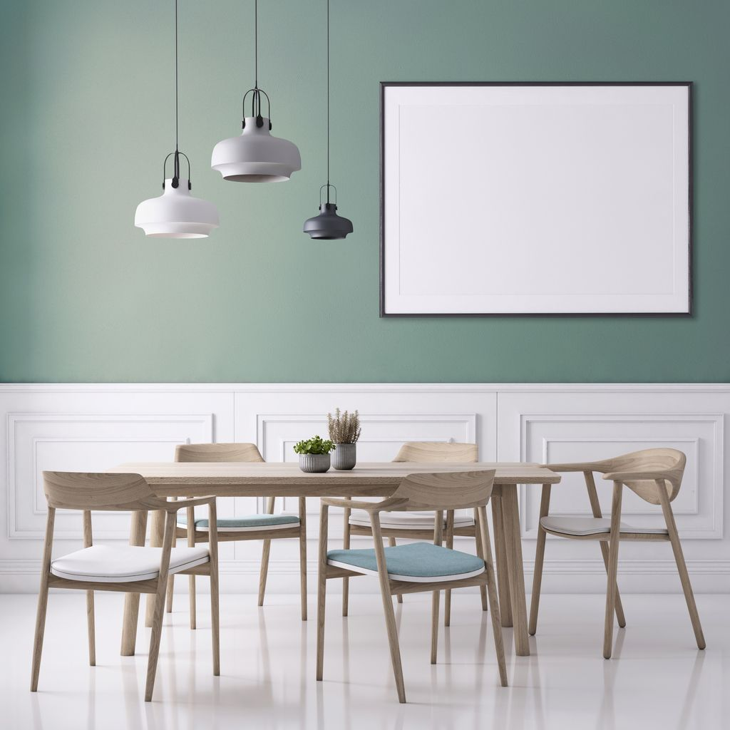 Dining room interior apartment with wooden chairs and table with plant. Pendant lamp, white polished floor and pastel colored wall with picture frame template for copy space.