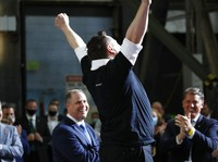 Tesla and SpaceX Chief Executive Officer Elon Musk jumps in the air as people applaud during an event at the Vehicle Assembly Building on Saturday, May 23, 2020, at NASAs Kennedy Space Center in Cape Canaveral, Fla. The event occurred after a rocket ship designed and built by SpaceX lifted off on Saturday with two Americans on a history-making flight to the International Space Station. NASA Administrator Jim Bridenstine looks on at left. (AP Photo/Alex Brandon)