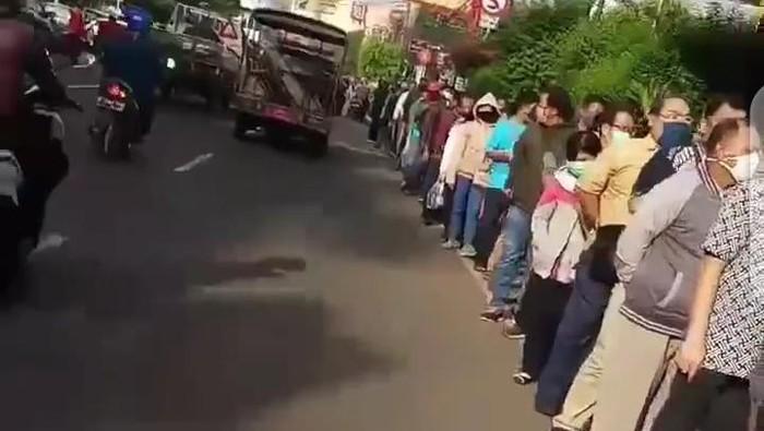 Antrean pemohon mengular hingga ke ruas jalan di depan kantor polisi.