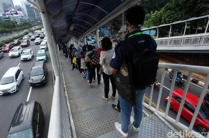 Antrean penumpang bus TransJakarta terlihat di Halte Gatot Subroto. Antrean itu disebabkan oleh warga yang kembali beraktivitas jelang penerapan new normal.