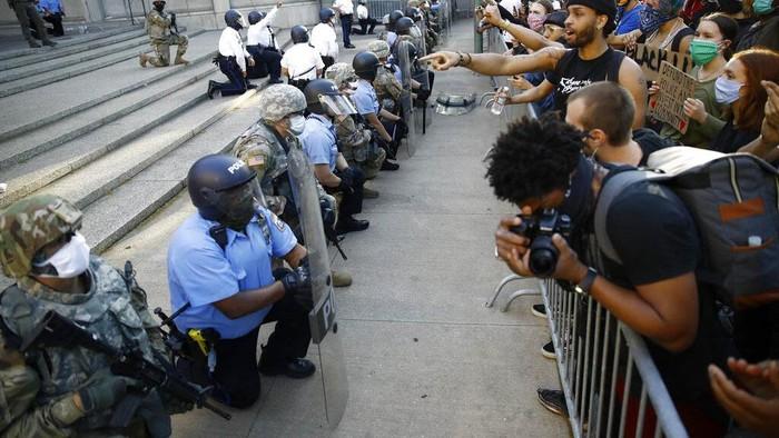 Aksi protes kematian George Floyd berujung rusuh di AS. Namun di beberapa lokasi sejumlah polisi justru menunjukkan solidaritas dengan berlutut bersama pendemo.