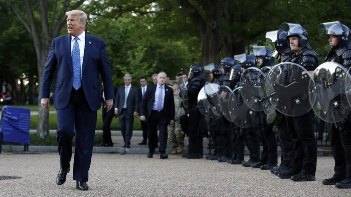 President Donald Trump walks past police in Lafayette Park after he visited outside St. Johns Church across from the White House Monday, June 1, 2020, in Washington. Part of the church was set on fire during protests on Sunday night. (AP Photo/Patrick Semansky)