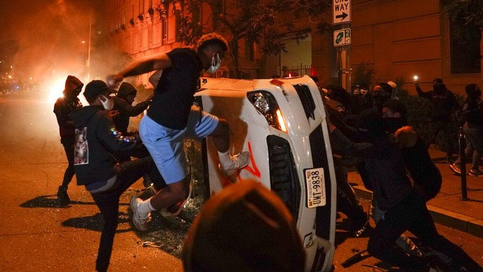 Police officers stop to look at a burned out police car, Monday, June 1, 2020, in the SoHo neighbourhood of New York. Protesters burned the car in reaction to George Floyds death while in police custody on May 25 in Minneapolis. (AP Photo/Mark Lennihan)