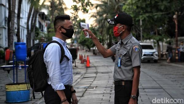 Beberapa pengunjung yang lewat kawasan ini wajib diperiksa suhu tubuhnya oleh para petugas.