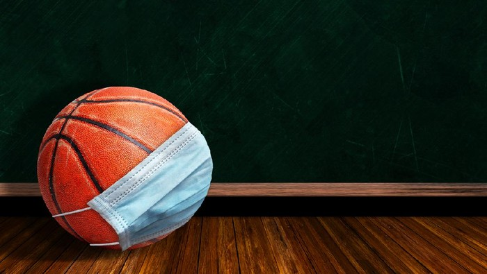 Basketball wearing surgical mask on a background chalk board with copy space for text. Concept of COVID-19 coronavirus pandemic affecting basketball seasons due to game or league suspensions or cancellations.
