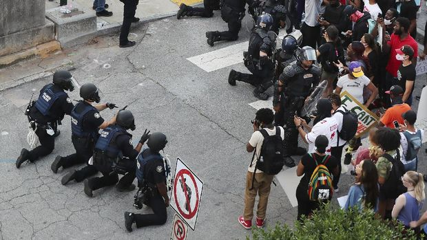 In a show of peace and solidarity, law enforcement officials with riot shields kneel in front of protesters Monday, June 1, 2020, during a fourth day of protests over the death of George Floyd in Minneapolis. (Curtis Compton/Atlanta Journal-Constitution via AP)