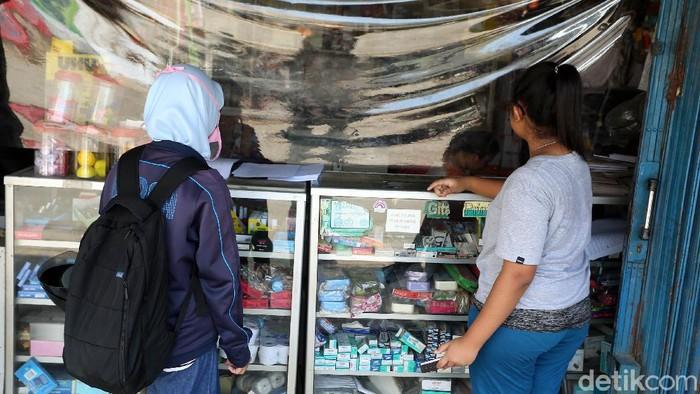 Meminimalisir penyebaran virus Covid-19 (Corona), warung dan toko di wilayah Kabupaten Bogor kini diberi tirai pembatas plastik.