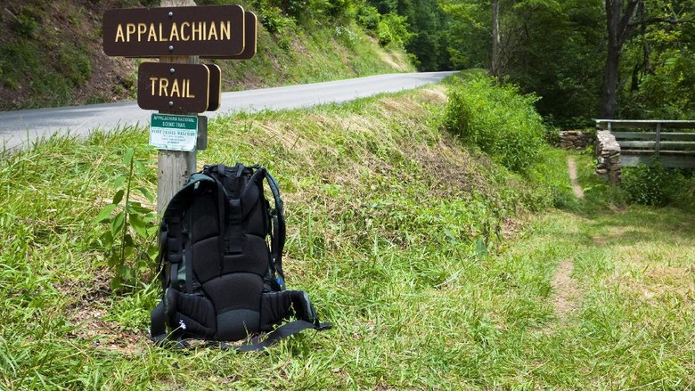 A backpackers pack rest against a signpost for the Appalachian Trail in southwest Virginia. The road is state route 650, several miles from Marion, VA. The trail crosses the road and goes across the footbridge seen on the right.