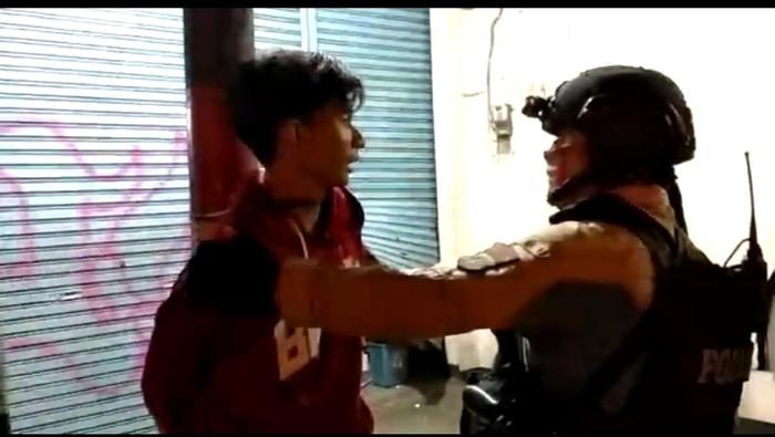 Polisi melepaskan ikatan tali yang mengikat pelaku di tiang listrik