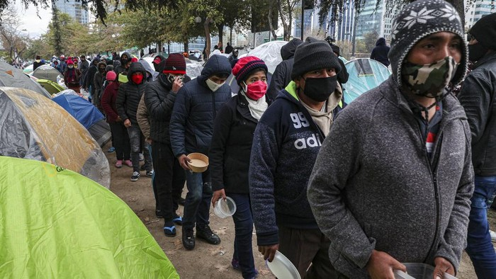 A Bolivian migrant pases a box milk while others in line up for a free lunch at a camp outside the Bolivian consulate to demand repatriation, amid the spread of the new coronavirus and lack of work in Santiago, Chile, June, Tuesday, 2, 2020. Citizens of Peru, Bolivia, Venezuela and Colombia living in Chile are camping in front of their respective consulates to demand that they help them to return home. (AP Photo/Esteban Felix)