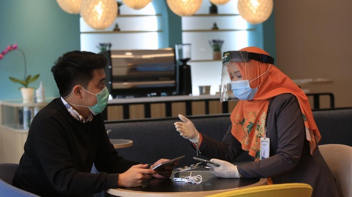 Persiapan hadapi new normal di tengah pandemi Corona dilakukan di sektor perbankan. Penggunaan masker jadi salah satu protokol kesehatan yang wajib dilakukan.