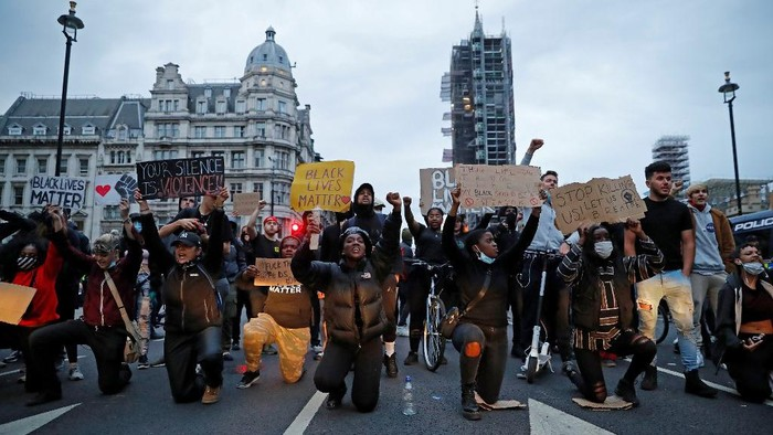 Protestors hold placards as they kneel in front of Police vans in Parliament Square, during an anti-racism demonstration in London, on June 3, 2020, after George Floyd, an unarmed black man died after a police officer knelt on his neck during an arrest in Minneapolis, USA. - Thousands of people took to the streets of London on Wednesday to protest the death of George Floyd in US police custody, as Prime Minister Boris Johnson condemned the killing and told President Donald Trump that racist violence had