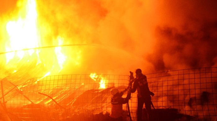 Petugas pemadam kebakaran berusaha memadamkan api yang membakar gudang ban di Desa Tenggeles, Kudus, Jawa Tengah, Rabu (3/6/2020). Kebakaran yang menghanguskan ribuan ban yang berada di gudang di pinggir jalan jalur pantura tersebut menyebabkan kemacetan panjang di jalur itu, sementara delapan unit mobil kebakaran dikerahkan untuk memadamkan kebakaran tersebut. ANTARA FOTO/Yusuf Nugroho/foc.
