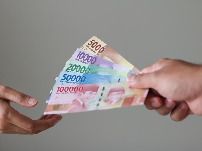 man hand show rupiah money on white background