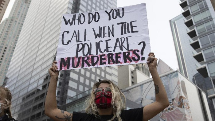 A woman holds up a sign during a demonstration in Los Angeles, Friday, May 29, 2020, in protest over the death of George Floyd, who died in police custody on Memorial Day in Minneapolis. (AP Photo/Christian Monterrosa)