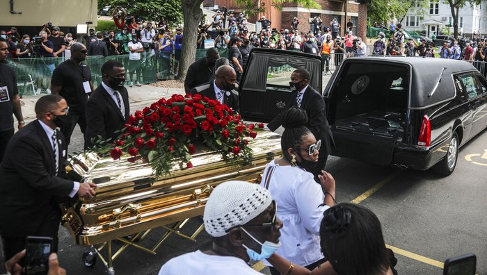 Members of the Congressional Black Caucus, at right, including Rep. Sheila Jackson-Lee, left, wearing blue face mask, U.S. Rep. Ilhan Omar, second from left, and U.S. Rep. Ayanna Pressley, right, stand at the casket of George Floyd before a memorial service at North Central University, Thursday, June 4, 2020, in Minneapolis. Floyd died on May 25 as a Minneapolis police officer pressed his knee into his neck, ignoring his cries and bystander shouts until he eventually stopped moving. (AP Photo/Bebeto Matthews)