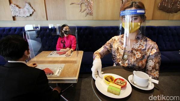 Pramusaji hotel Sunan menggunakan kaos tangan, tameng wajah, dan masker saat menyajikan makanan.