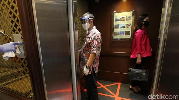 Karyawan hotel dan tamu tetap menjaga jarak sesuai protokol ksehatan.