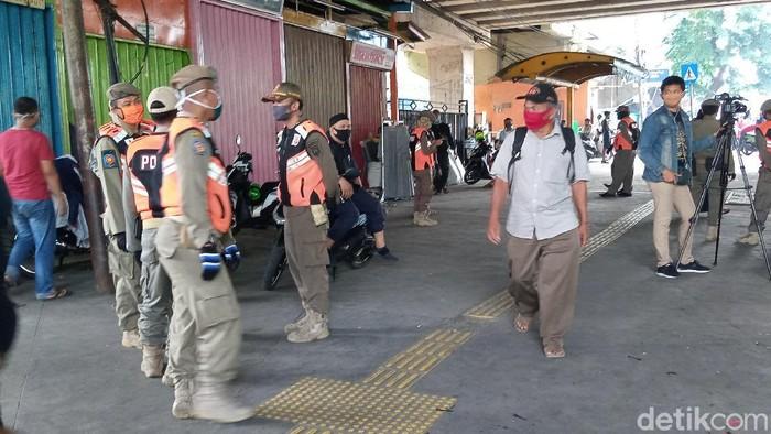 Personel Satpol PP menertibkan PKL di trotoar pasar Tanah Abang, Jakarta.
