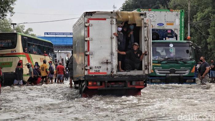 Berbagai upaya dilakukan warga untuk dalam menerobos banjir di Pelabuhan Nizam Zachman, Muara Baru, Jakarta Utara. Mulai dari memakai jasa gerobos hingga menumpang truk.
