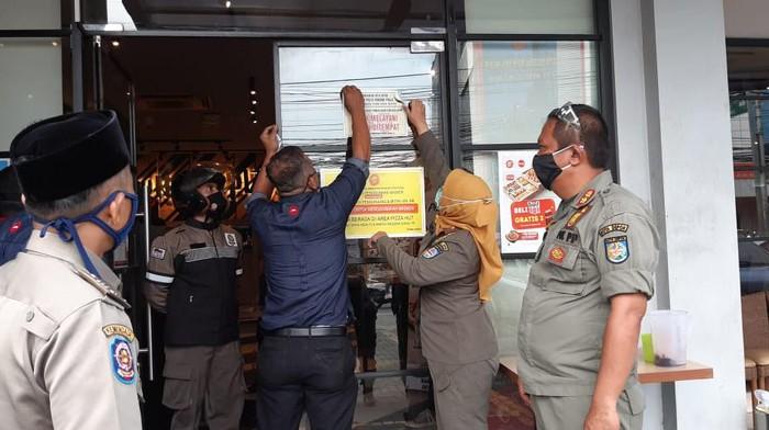 Satpol PP Depok Lepas Stker Larangan Makan di Tempat