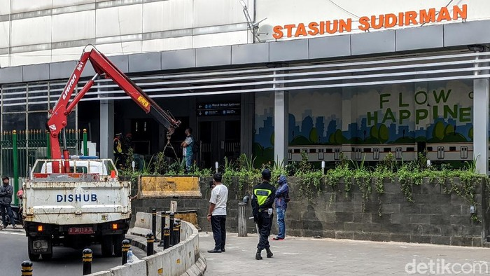 Depan Diberi Pembatas Beton ----   Petugas menurunkan road barrier beton, di depan akses Stasiun Sudirman, Jl Kendal, Jakarta, Jumat (5/6/2020).