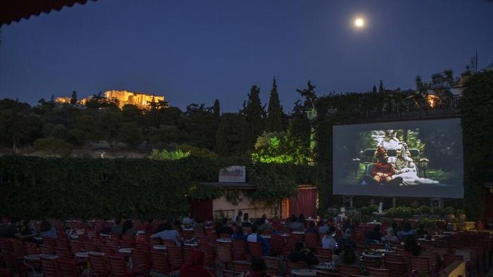 Beragam cara dilakukan warga dunia untuk hadapi new normal di tengah pandemi COVID-19. Salah satunya dengan membuka bioskop terbuka seperti yang ada di Yunani.