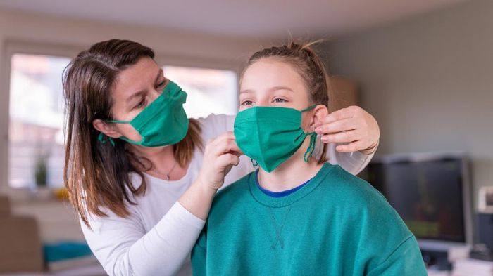 Mother wearing a green homemade protective face mask and putting one to her daughter at home during the coronavirus Covid-19.
