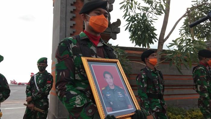 Prajurit TNI memegang foto mendiang Kapten Cpn I Kadek Udi Suardiasa. (Angga Riza/detikcom)