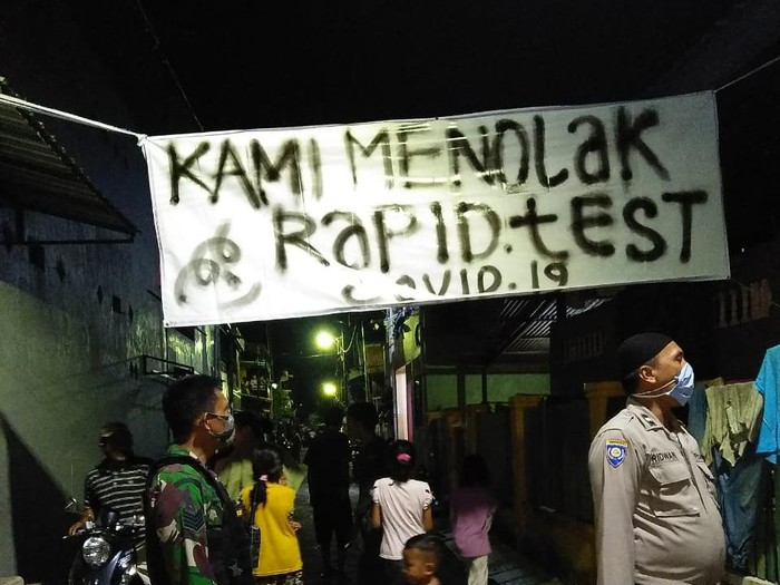 Aparat mencopot spanduk warga menolak rapid test (dok. Istimewa).