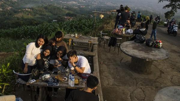 Pengunjung menikmati suasana pemandangan di salah satu saung kawasan wisata Caringin Tilu, Kabupaten Bandung Jawa Barat, Minggu (7/6/2020). Kawasan Wisata perbukitan Cartil kembali dibuka dengan kenormalan baru karena tidak termasuk dalam PSBB Parsial di Kabupaten Bandung. (ANTARA FOTO/NOVRIAN ARBI)
