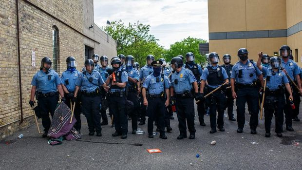 (FILES) In this file photo taken on May 27, 2020 Minneapolise Police officers stand in a line while facing protesters demonstrating against the death of George Floyd outside the 3rd Precinct Police Precinct in Minneapolis, Minnesota. - Members of the Minneapolis City Council announced on June 7, 2020 that they intend to disband the city's police department, US media reported. (Photo by Kerem Yucel / AFP)
