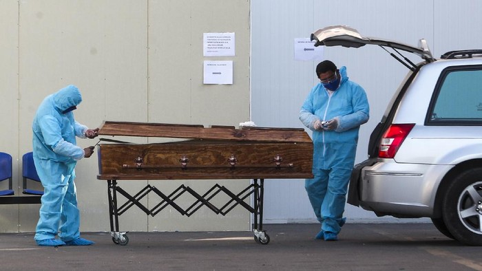 Funeral workers wearing protective gear as a precaution against the spread of the new coronavirus, prepare to receive the remains of a person who has died from the new coronavirus, at the San Jose hospital in Santiago, Chile, Tuesday, May 26, 2020. (AP Photo/Esteban Felix)