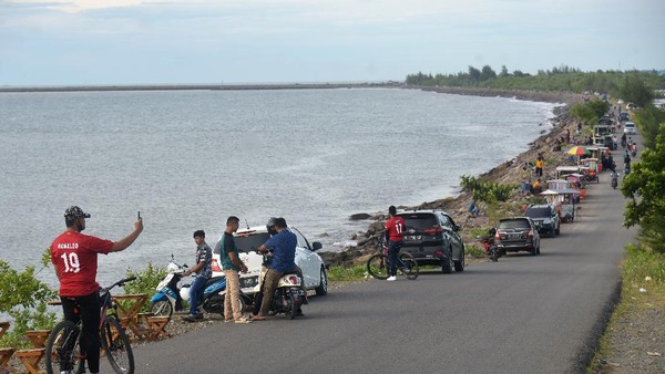 Pengunjung menikmati suasana di kawasan wisata pantai Ulee Lheue dan Kampung Jawa, Banda Aceh, Aceh, Minggu (7/6/2020). Sejumlah objek wisata pantai di daerah tersebut kembali ramai pengunjung dan pedagang kuliner keliling, tapi sebagian besar tidak menerapkan protokol kesehatan untuk mencegah penyebaran COVID-19. (ANTARA FOTO/Ampelsa/aww..(ANTARA FOTO/AMPELSA)