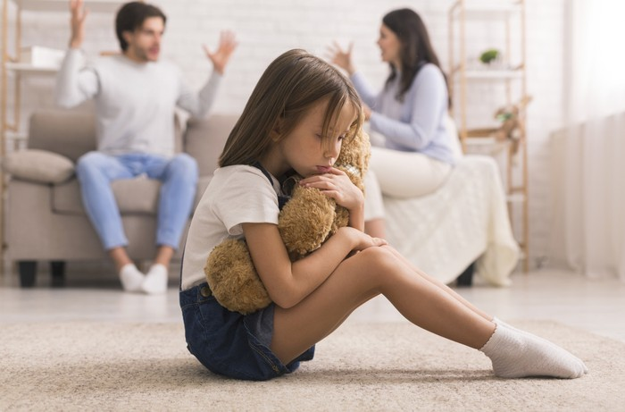 Family Problems. Cute Little Girl Suffering From Parents Arguing, Sitting On Floor With Teddy Bear, Feeling Abandonned And Lonely