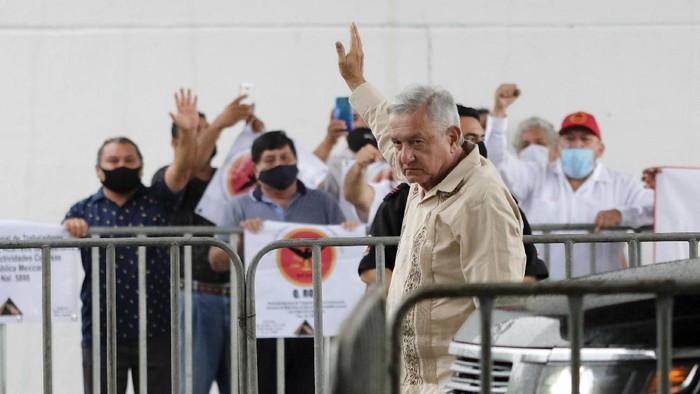 Mexican President Andres Manuel Lopez Obrador waves to supporters in Lazaro Cardenas, Quintana Roo state, Mexico, Monday, June 1, 2020. Amid a pandemic and the remnants of a tropical storm, President Lopez Obrador kicked off Mexicos return to a