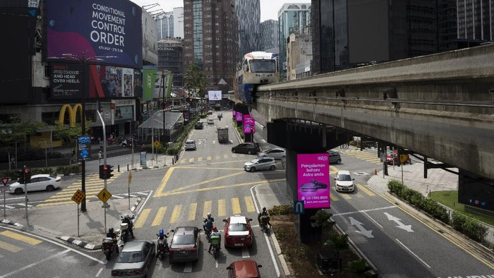 A LRT (Light Rain Transit) passes by a signboard road conditional movement control order in downtown Kuala Lumpur, Malaysia, on Sunday, June 7, 2020. Malaysian government has lifted the conditional movement order (CMCO) and replaced it with a recovery movement control order effective June 10 until Aug. 31. (AP Photo/Vincent Thian)