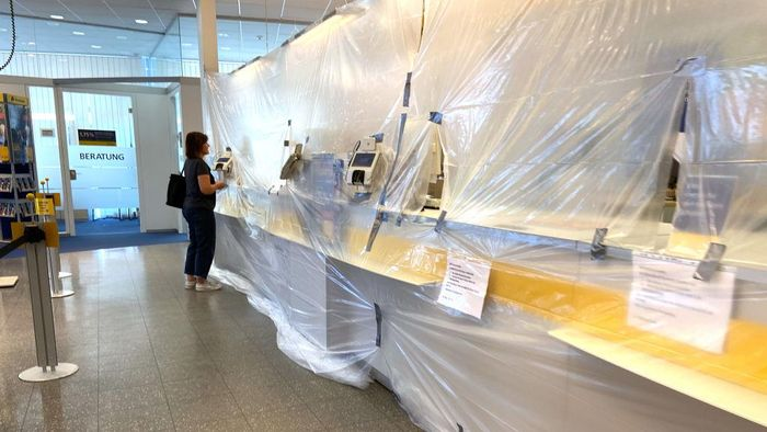 ERDING, GERMANY - MARCH 18: Employees of a post office have protected themselves with plastic foil in their post office on March 18, 2020 in Erding, Germany. Everyday life in Germany has become fundamentally altered as authorities tighten measures to stem the spread of the coronavirus. Public venues such as bars, clubs, museums, cinemas, schools, daycare centers and universities have closed. Many businesses are resorting to home office work for their employees. And travel across the border to most neighbouring countries is severely restricted.  (Photo by Alexander Hassenstein/Getty Images)