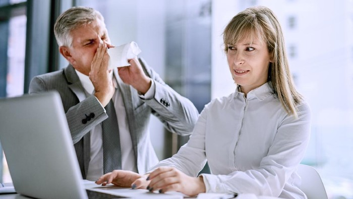 Shot of a sick businessman sneezing in front of a businesswoman in the office