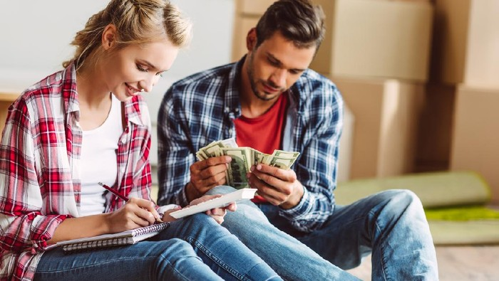 young couple counting money while sitting on floor in new apartment